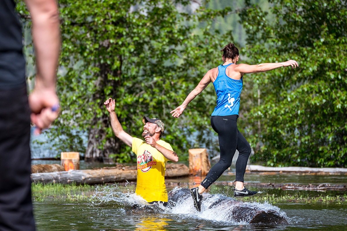 A woman running on a log floating in water during Kaslo Logger Sports