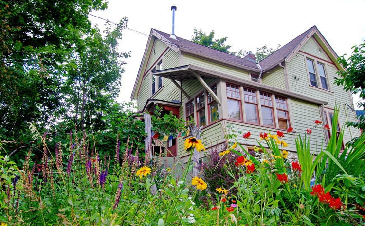 A heritage home in Nelson, BC with flowers in the foreground