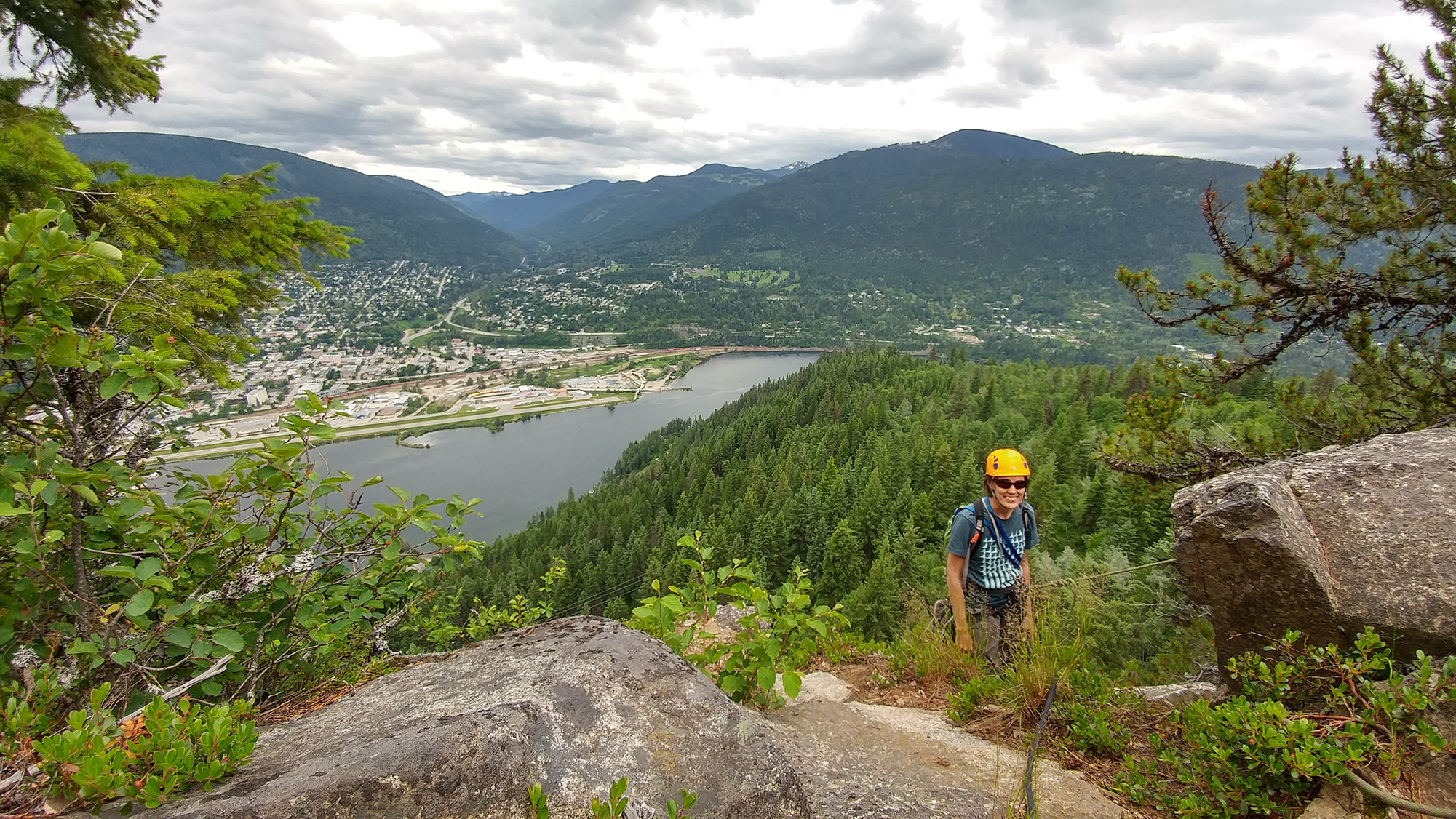 A climber standing on Pulpit Rock with a view of Nelson, BC below.