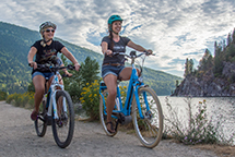 Two girls riding e-bikes on Nelson's waterfront pathway.