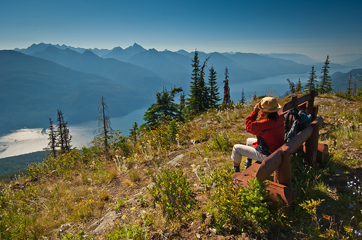 A person sitting on a hand-crafted wooden bench at the top of Mount Buchanan, looking down along Kootenay Lake