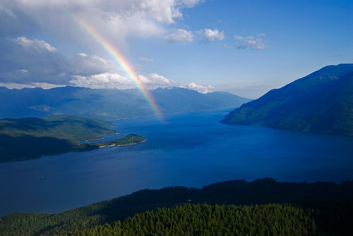 View of Kootenay Lake with rainbow arching over it