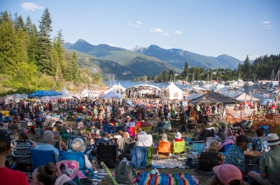 A crowd of people watching musicians on the floating stage at Kaslo Jazz Festival.