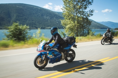 A person on a motorcycle riding along Kootenay Lake, BC