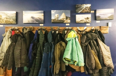A rack of winter jackets below some canvas prints of snowy mountains in Nelson BC