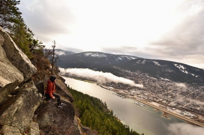 A woman sitting on pulpit rock, looking down on Nelson BC far below