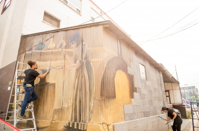 Two artists painting a mural during the Nelson International Mural Festival