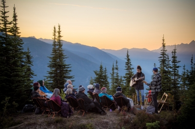 Artist Tenise Marie singing to a small crowd on the top of Mt Buchanan in Kaslo, BC at sunset.