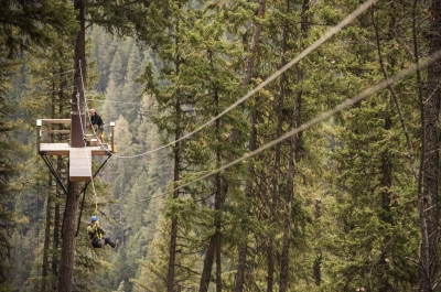 A person zip lining through the trees at Kokanee Mountain Zipline in Nelson, BC.