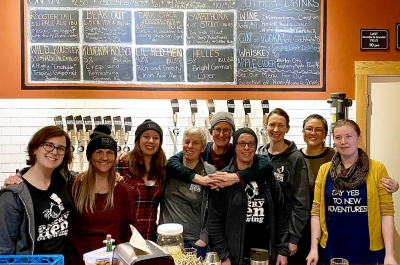 Smiling staff behind the bar at Angry Hen Brewing.