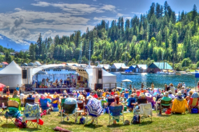 Audience enjoying Kaslo jazz festival stage with mountains and lake in the background