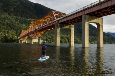 A man stand up paddle boarding under the Big Orange Bridge in Nelson, BC.