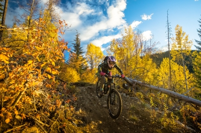 A person riding down a steep mountain bike trail surrounded by vibrant fall colours.