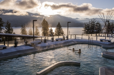 Two people in the main pool at Ainsworth Hot Springs Resort on a sunny winter day.