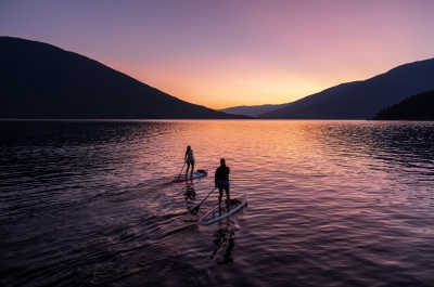 Two paddle boarders on Kootenay Lake paddling into the sunset