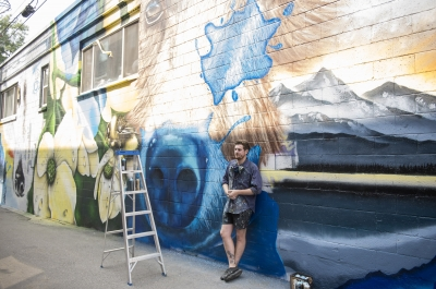 Artist Jerome Davenport stands in front of his mural at the 2018 Nelson International Mural Festival.