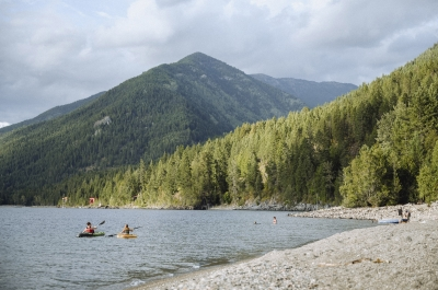 Kayakers and people on the beach with mountains in the backcountry at Lockhart Beach Provincial Park near Crawford Bay, BC