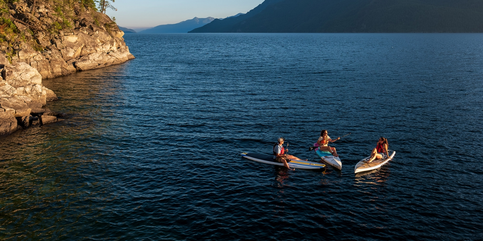 Three paddle boarders sitting on their boards facing each other on Kootenay Lake, BC
