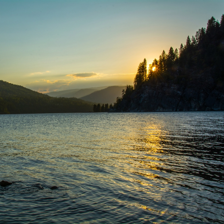 The sun setting behind trees on the shore of Kootenay Lake