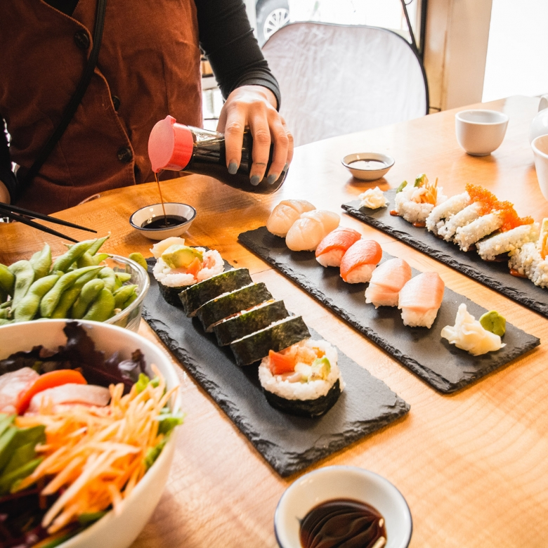 Hands pouirng soy sauce into a small dish with a table full of colourful sushi.