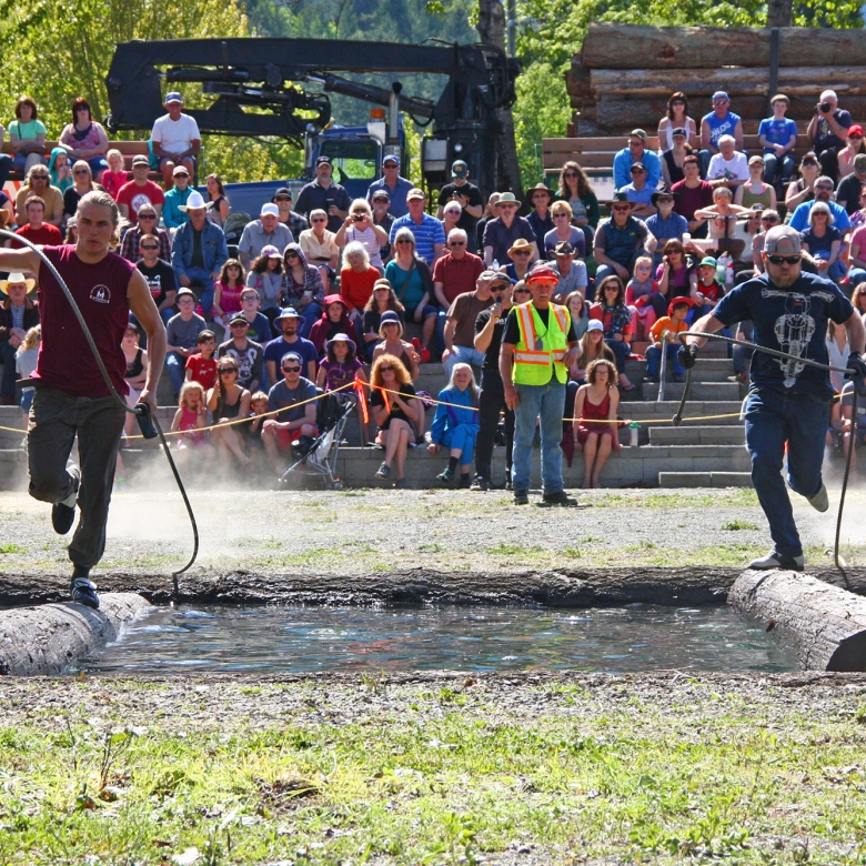 Two men running on a log in water during Kaslo Logger Sports at May Days in Kaslo, BC.