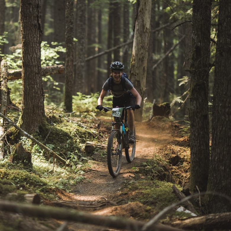 A girl biking in the forest outside of Kaslo. Biking near Nelson, BC.