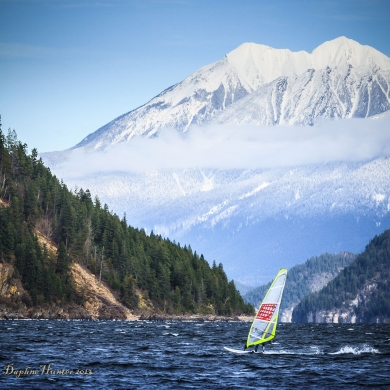 Windsurfer on Kootenay Lake, with treed mountainside and snow-covered mountain in the background