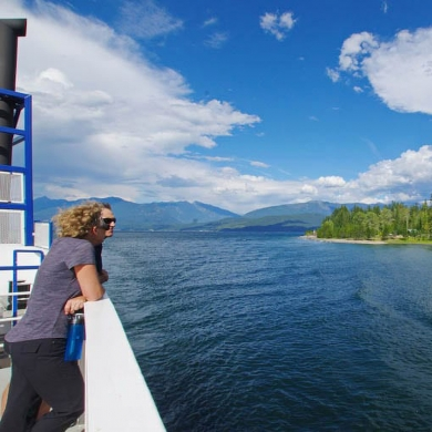 Two people on a ferry looking over the side at the lake on a sunny day, enjoying things to do near Nelson BC