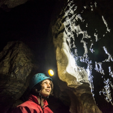 A person with a helmet and headlamp on looking up at a wall inside Cody Caves, near Nelson BC