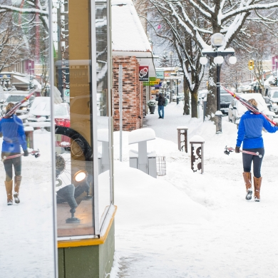 Woman walking downtown Nelson BC carrying cross country skis