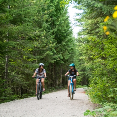Two women cycling on the Great Northern Rail Trail above Nelson, BC on an ebikes