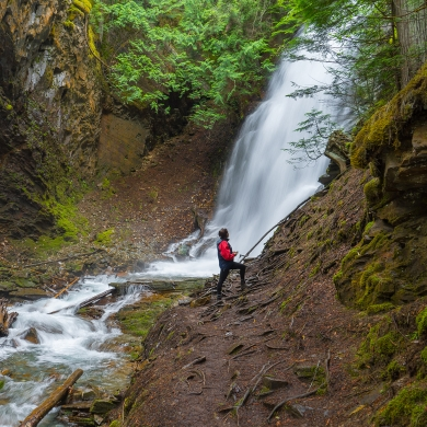 A hiker standing in front on the Insta-worthy Fletcher Falls near Kaslo, BC