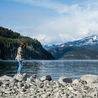 A girl standing on a rock on the beach in Kaslo, BC