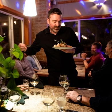 Diners enjoying food at night at Sage Taps and Wine Bar in Nelson, BC