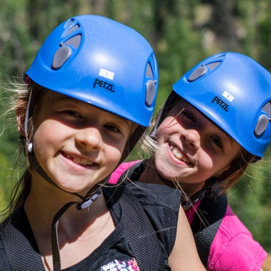 Two children with blue helmets on Kokanee Mountain Zipline near Nelson BC