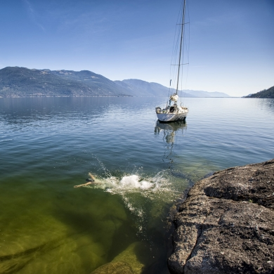 Jumping into Kootenay Lake with a sailboat in the background.