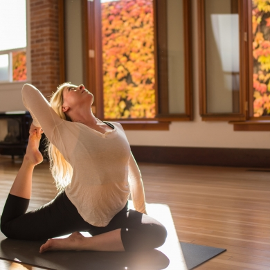 Someone doing yoga in a Nelson, BC studio with vibrant fall colours in the windows.