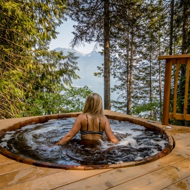 A person in the cedar hot tub at the Sentinel in Kaslo, BC