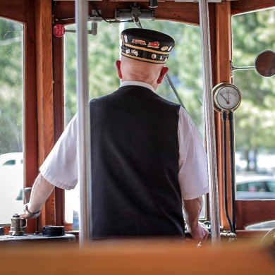 Looking through the front windows of Streetcar #23 with the driver in uniform in the foreground.
