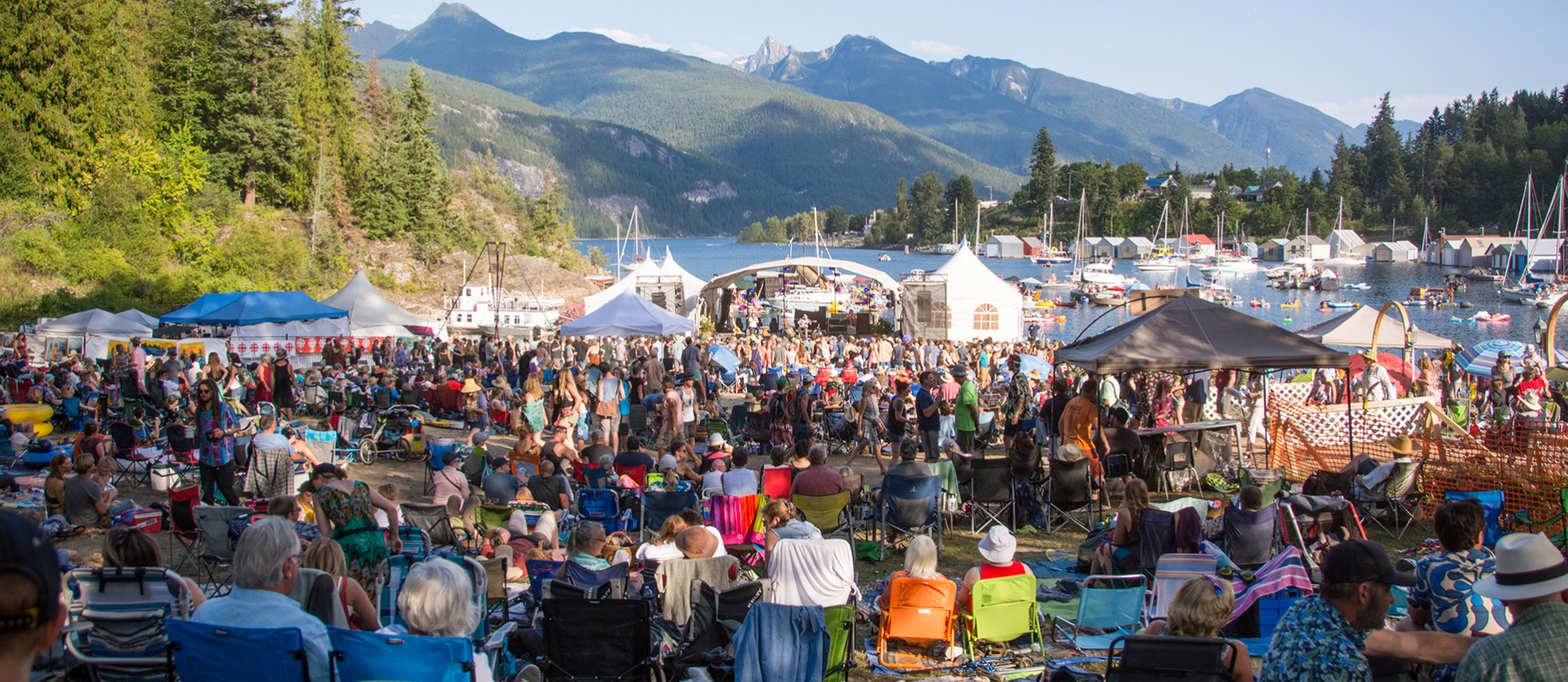 People sitting on the grass looking towards the floating stage on a sunny day at kaslo jazz festival