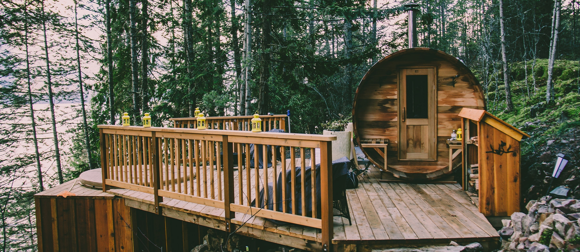A cylindrical cabin next to a hot tub set into a wooden deck, overlooking Kootenay Lake