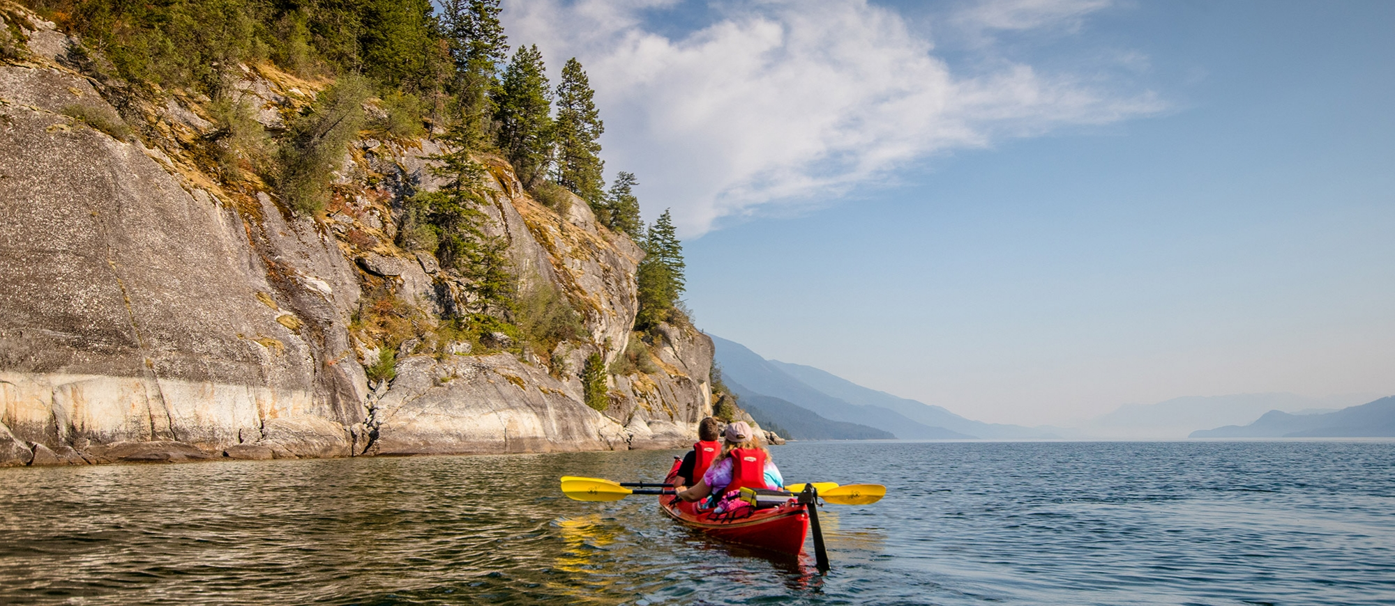 Two people on a double kayak paddling on Kootenay Lake near Kaslo, BC