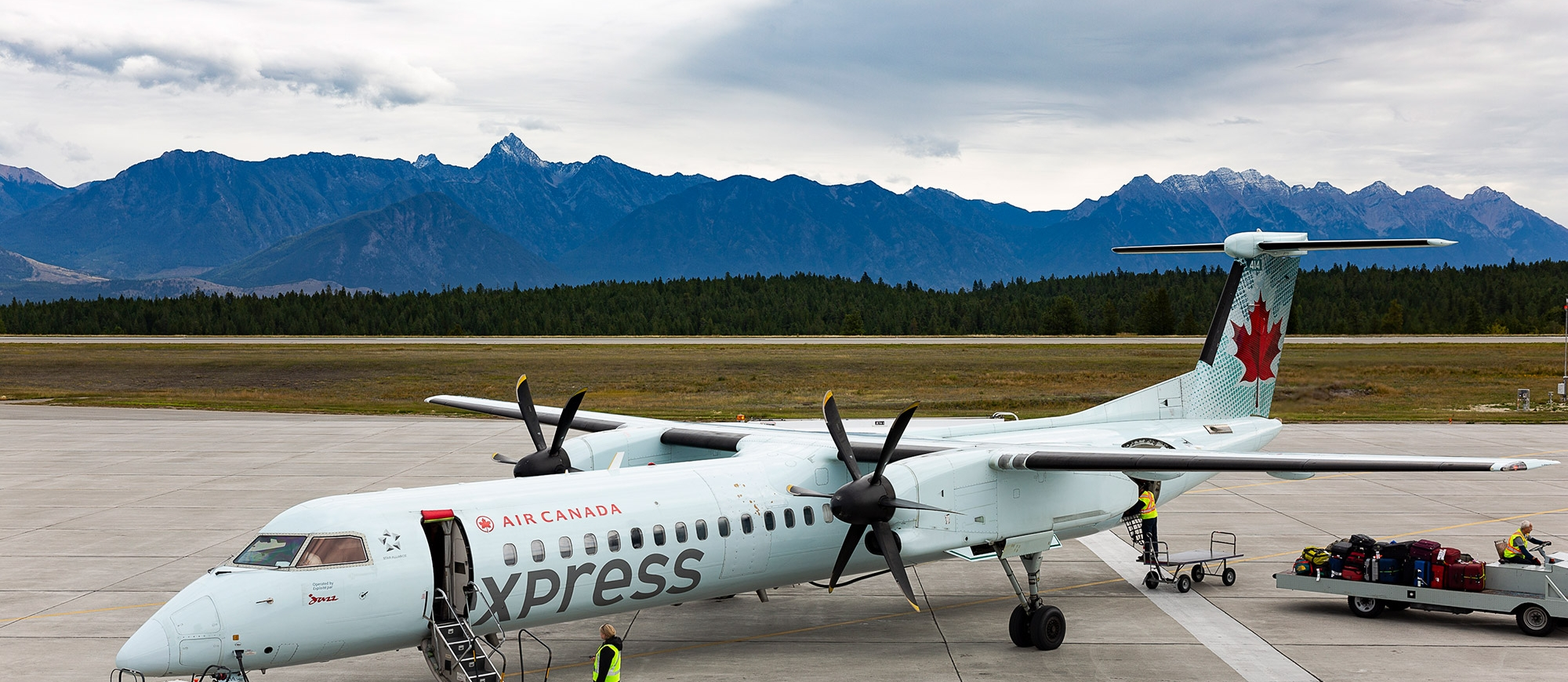 A plane with mountains in the background Canadian Rockies International Airport in Cranbrook, BC