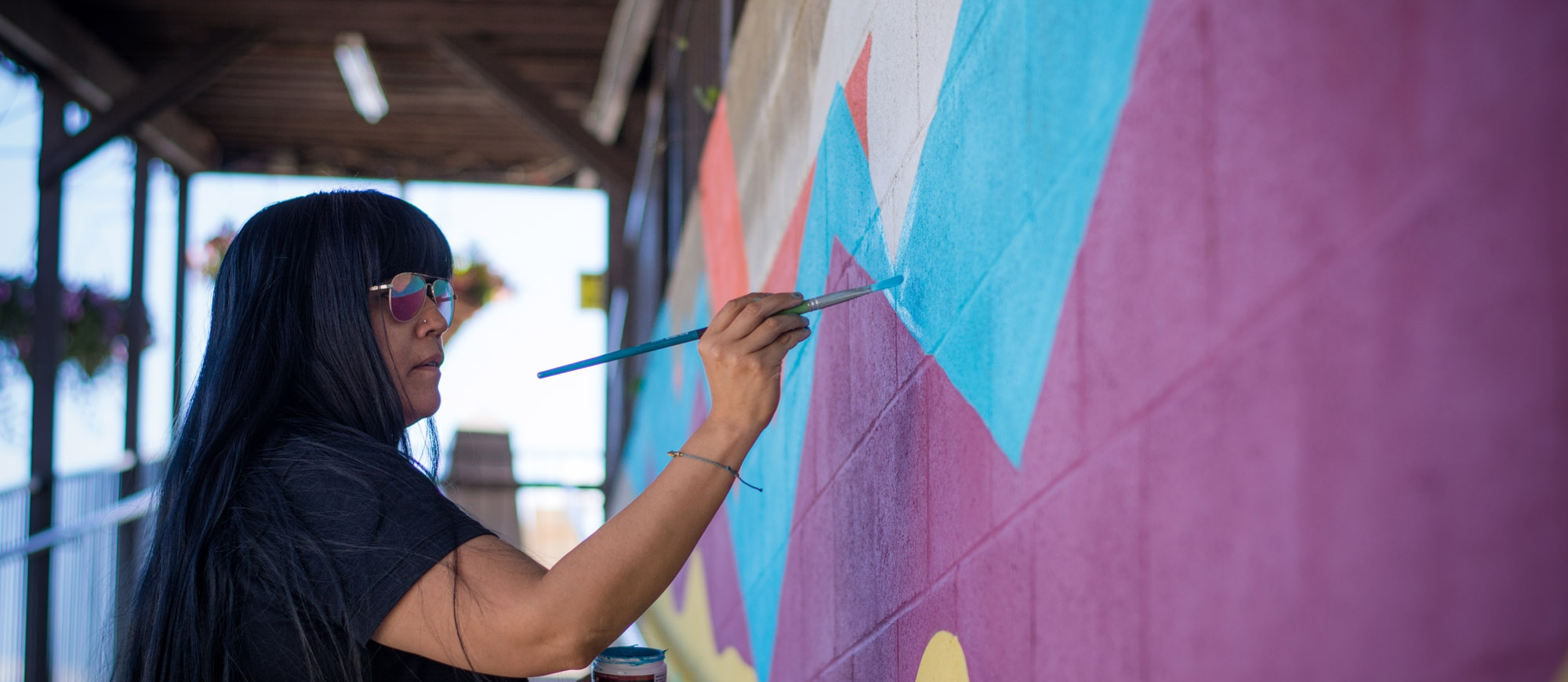 An artist painting a colourful mural at Ainsworth Hot Springs REsort