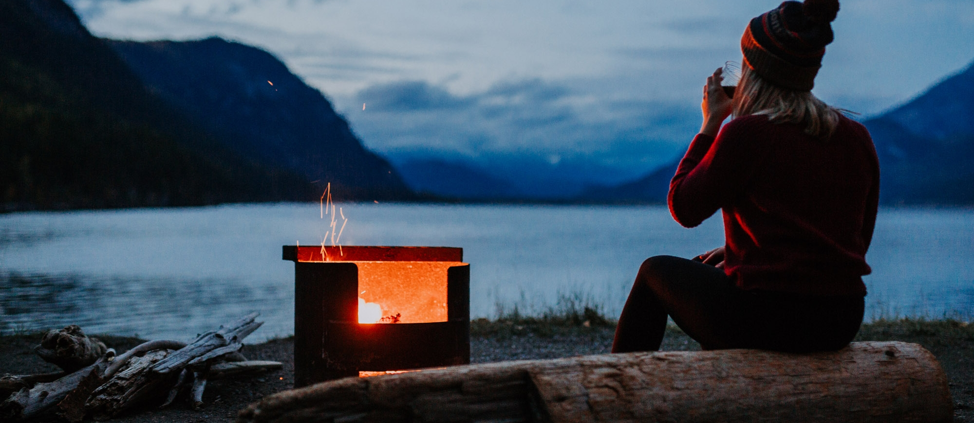 A girl sitting by a campfire on the shores of Kootenay Lake, BC.
