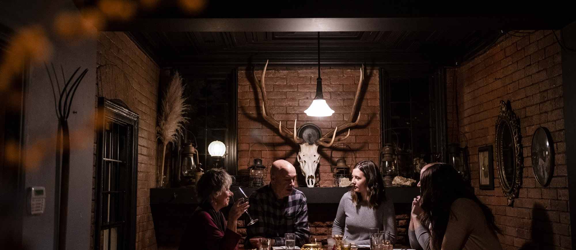 Four people sit around a candle lit table at Pitchfork Eatery in Nelson, BC
