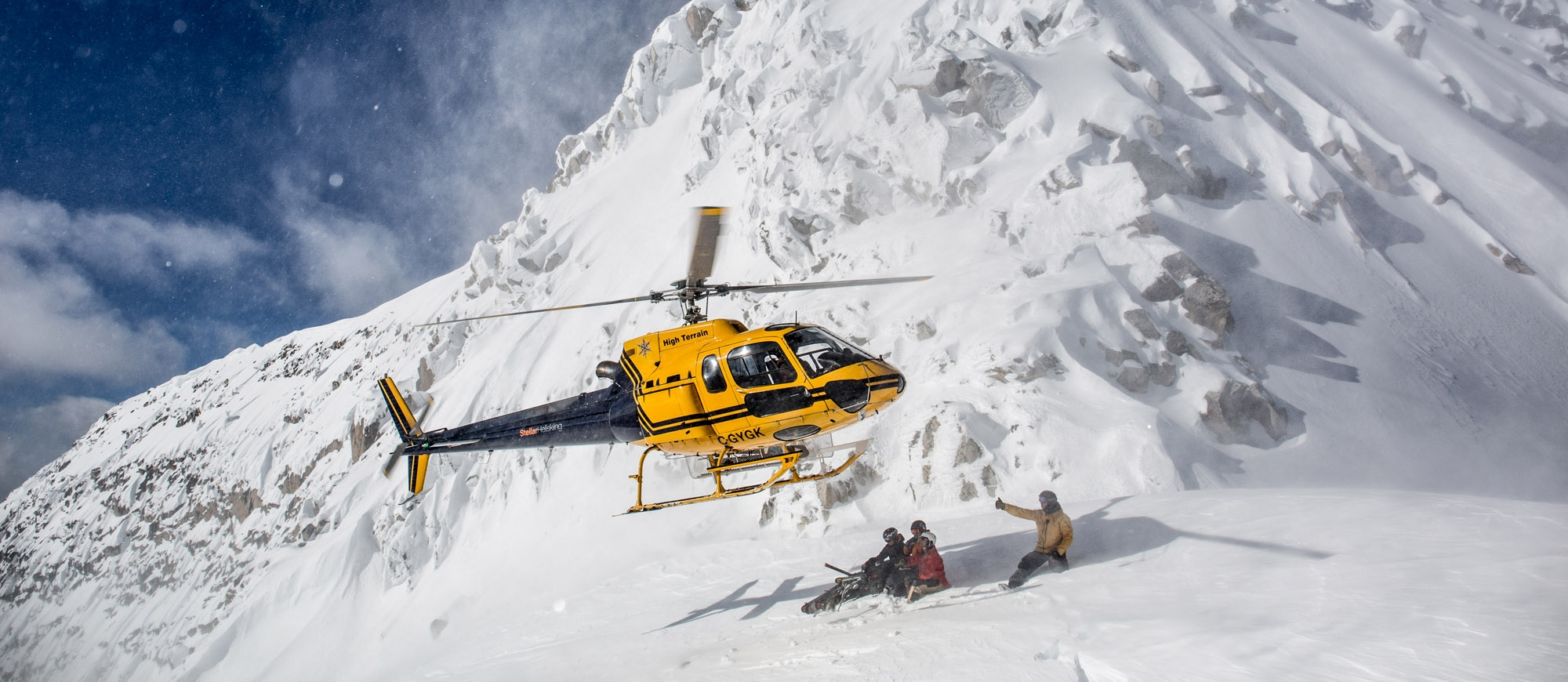Skiiers crouched down while a Stellar Heliskiing heli lands in the mountain near Kaslo, BC.