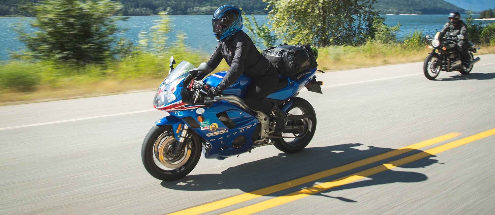 A motorcycle driving on the highway along the shores of Kootenay Lake.