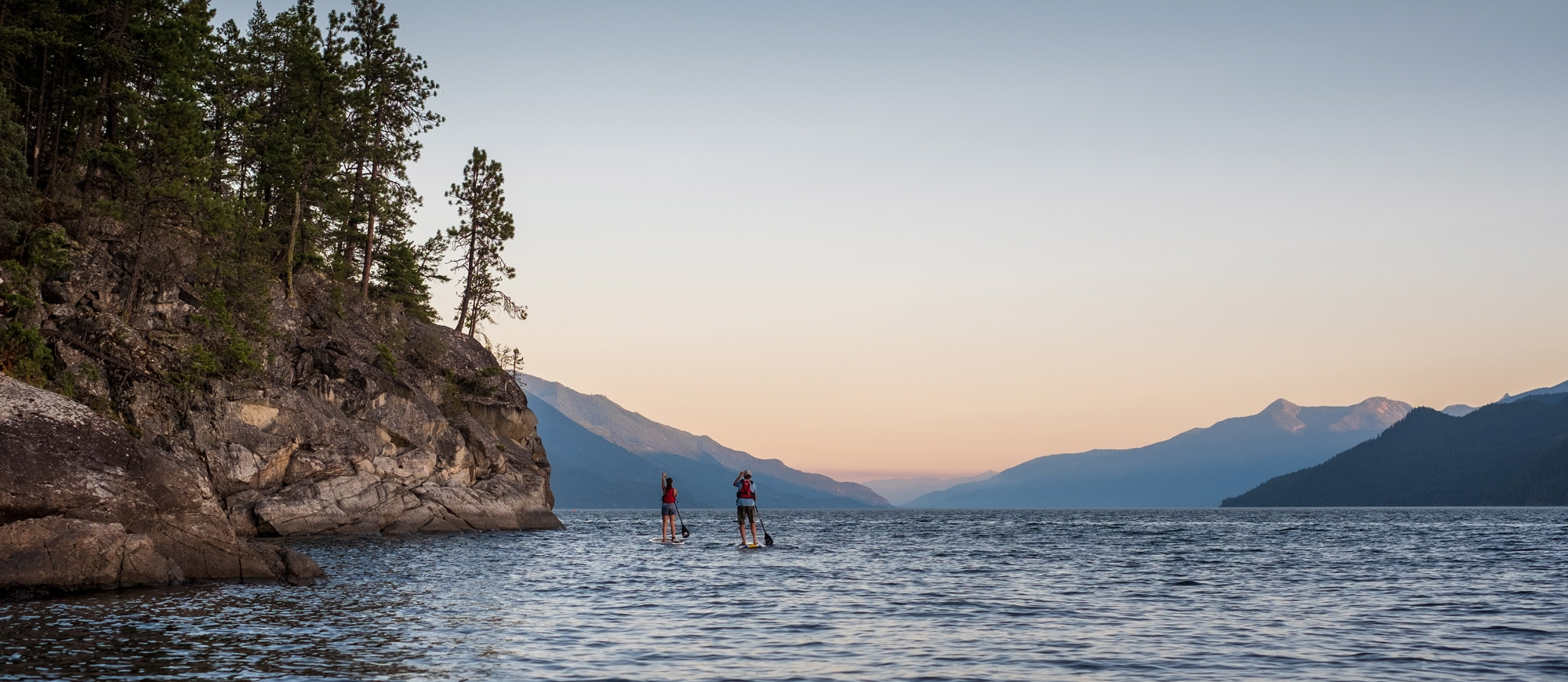Two stand up paddle boarders on the East Shore of Kootenay Lake, BC.