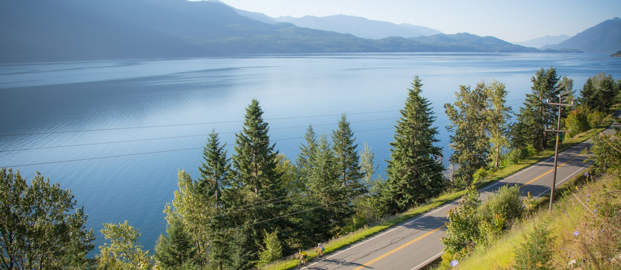 Two cyclists riding along the Highway near Kaslo, BC
